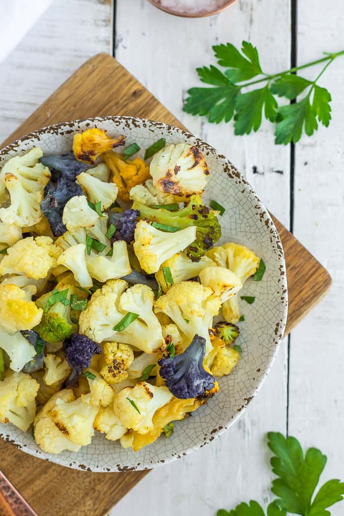 a plate with colorful roasted cauliflower on a white wooden board