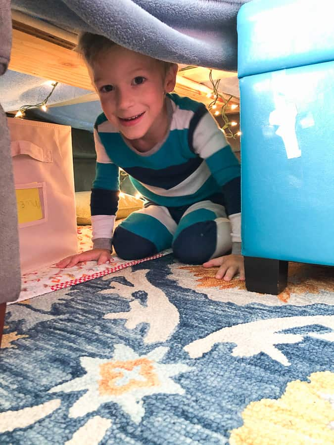 a boy in a blanket fort