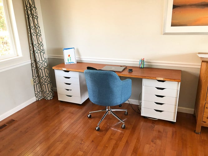 a white desk with a wooden top and a blue desk chair