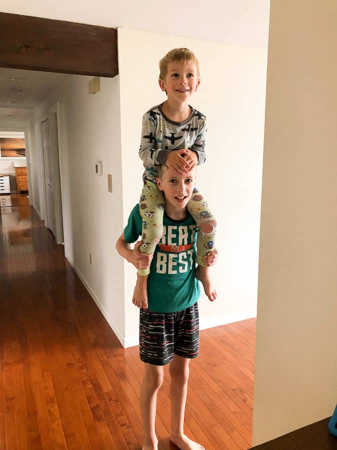 a boy giving another boy a ride on his shoulders