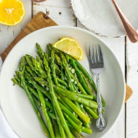 a plate of asparagus with a fork and a lemon wedge