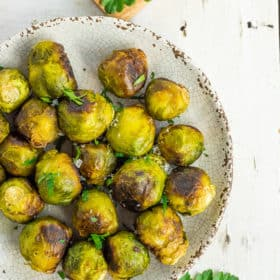 a grey plate with roasted frozen brussel sprouts topped with minced parsley