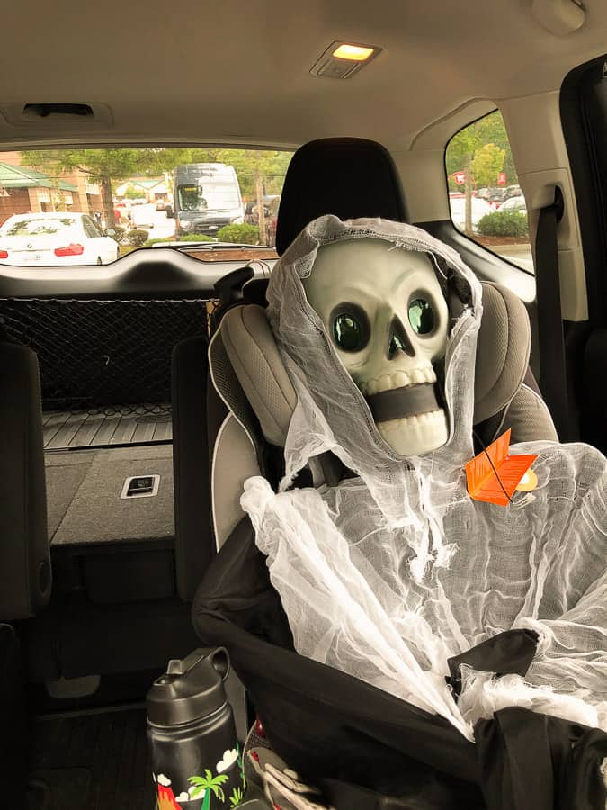 a skeleton in a carseat