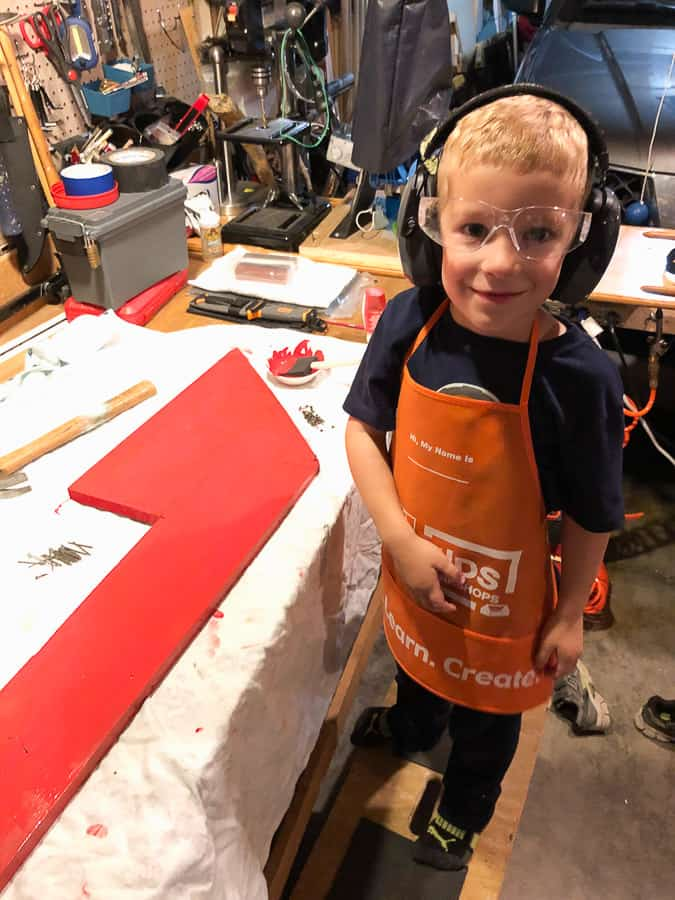 a boy in a Home Depot apron with safety glasses