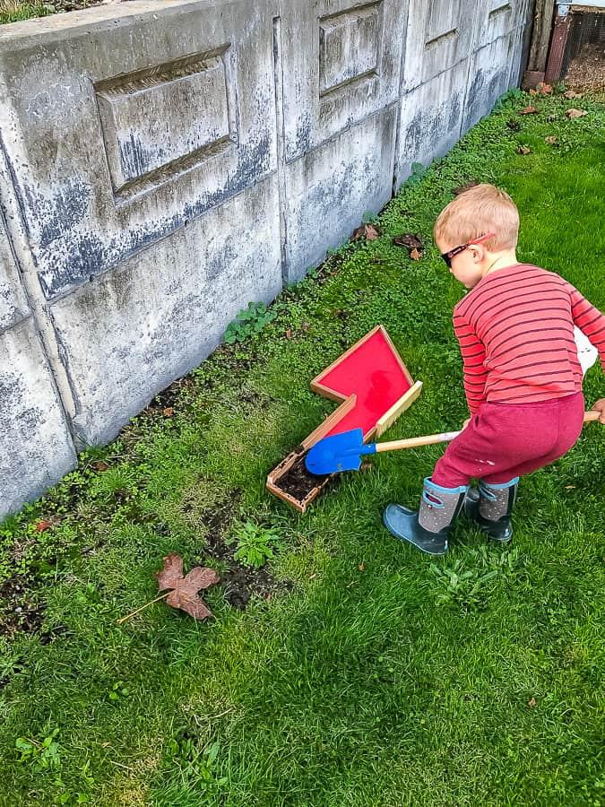 a boy shoveling on a lawn