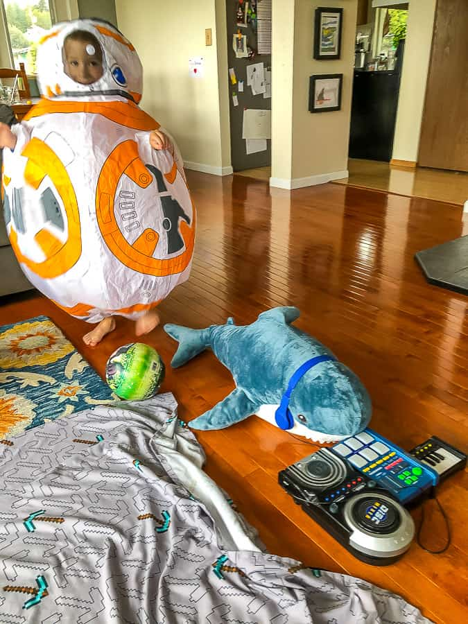 a boy in a BB8 costume with a stuffed shark