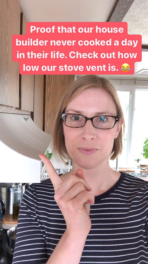 a woman standing in a kitchen pointing to a low oven vent