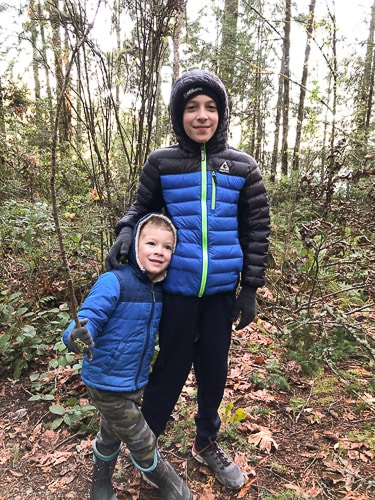 2 boys in blue coats in the woods