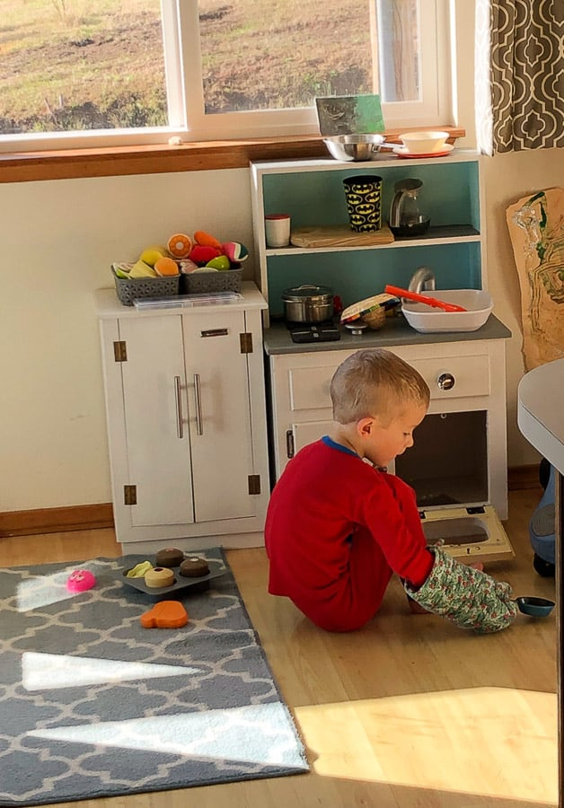 a boy in pajamas in a play kitchen