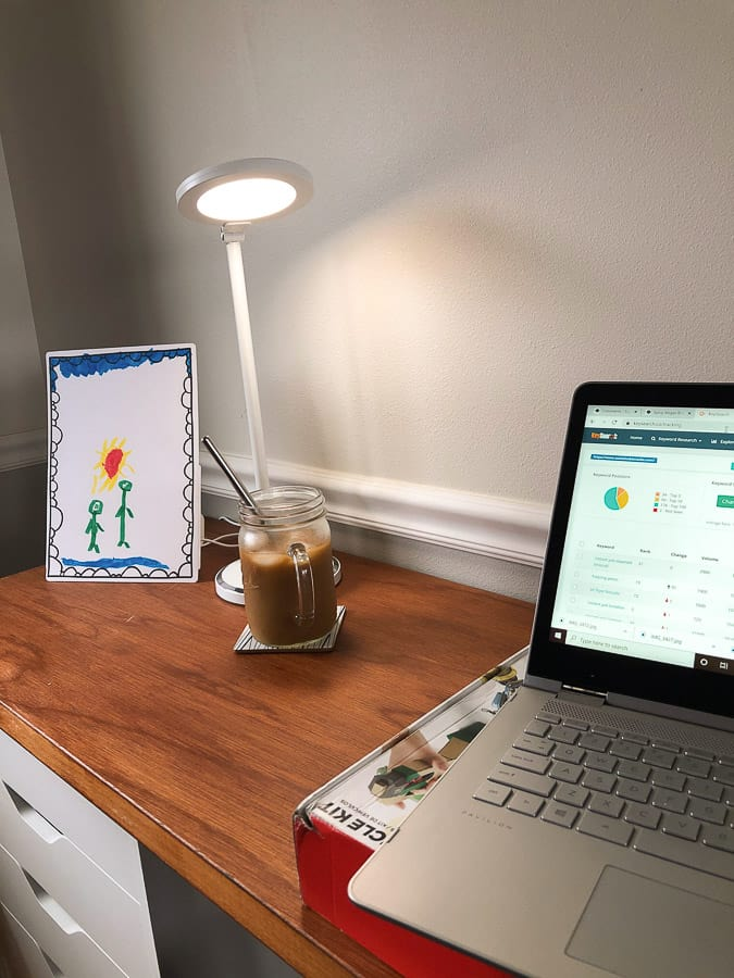 a lamp near a computer and glass of iced coffee