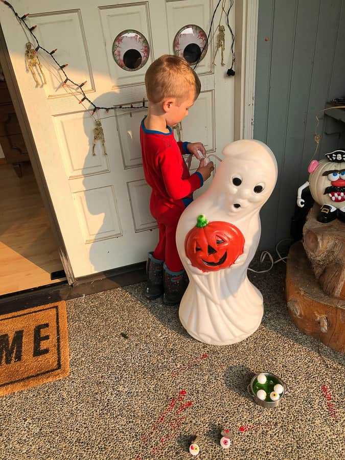 a boy on a porch with Halloween decorations