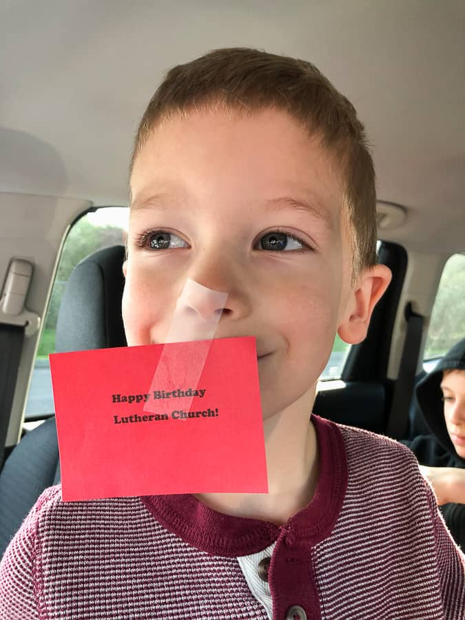 a boy with a red sign taped to his nose