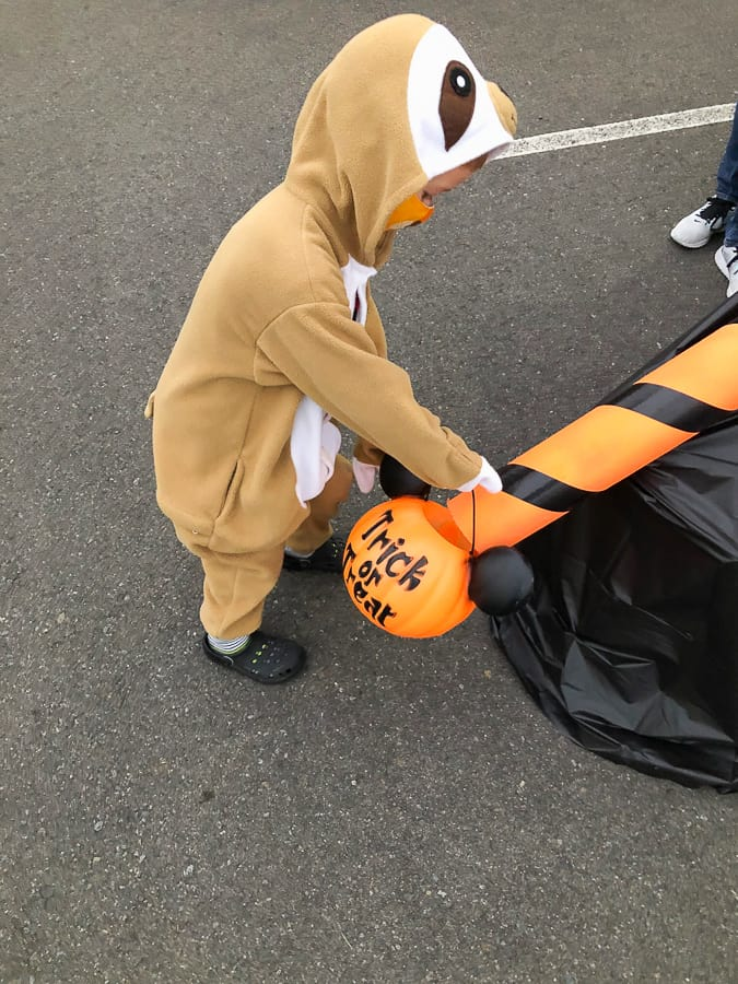 a kid in a sloth costume with a candy bucket