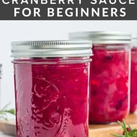 3 jars of homemade canned cranberry sauce with fresh cranberries on a white board