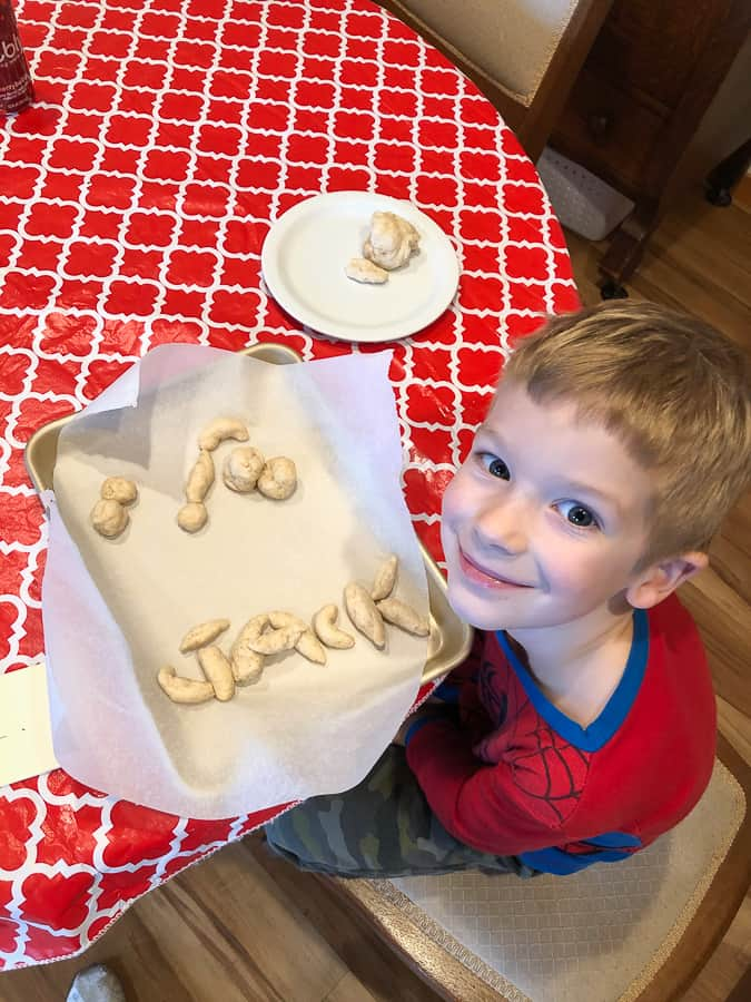 "a boy with bread dough that spells ""Jack"""