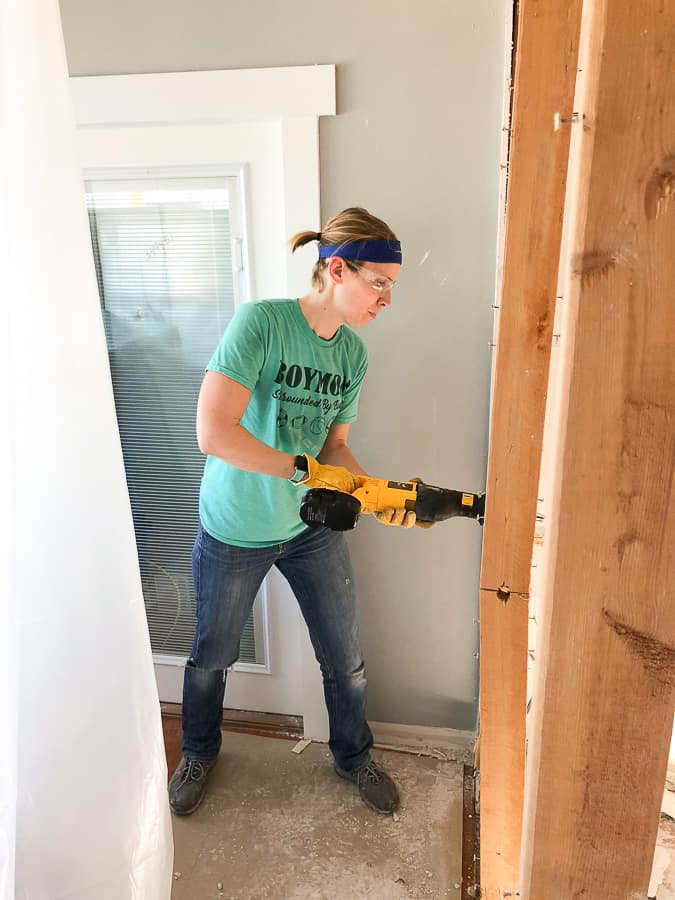 a woman in a blue shirt using power tools