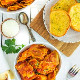 a white bowl of instant pot ravioli with garlic bread and fresh parsley