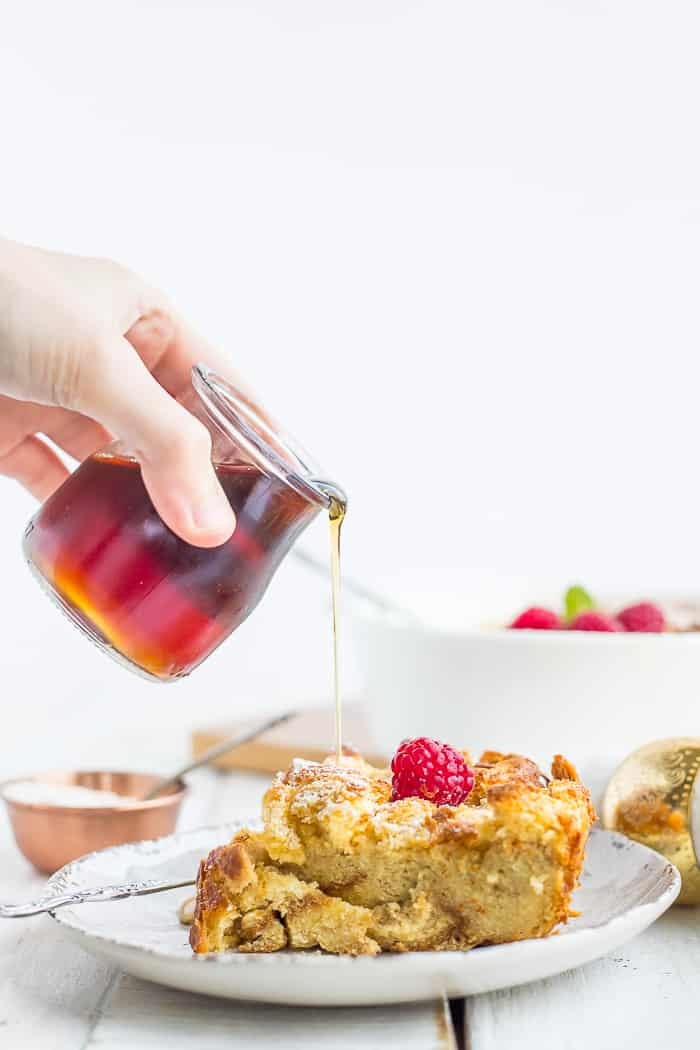 maple syrup being poured over a plate of bread pudding