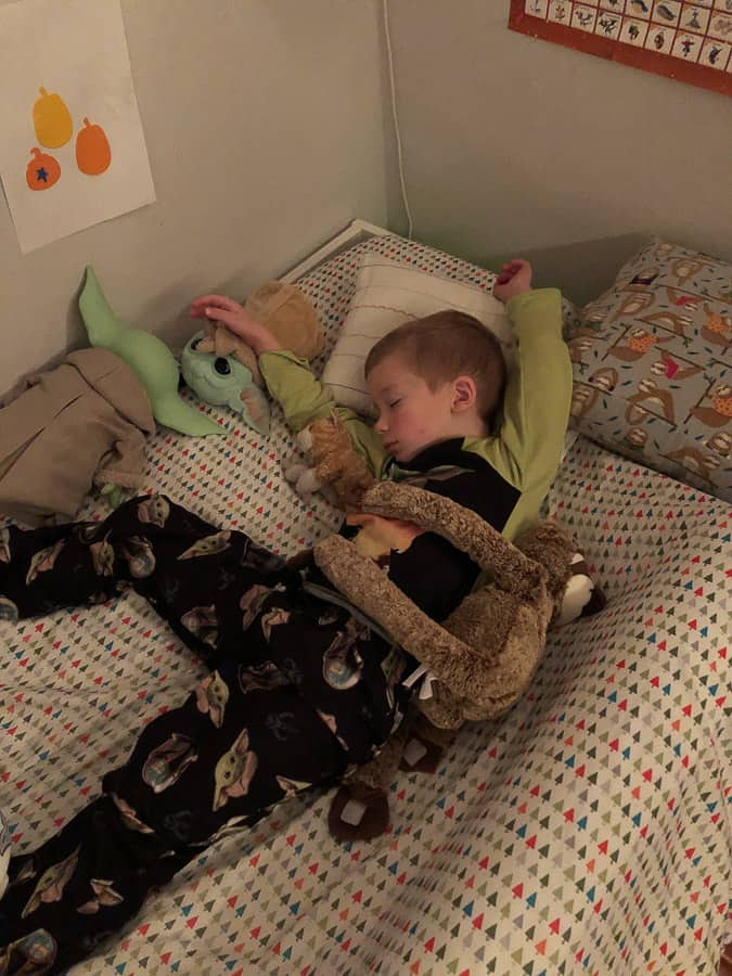 a kid sleeping with lots of stuffed animals