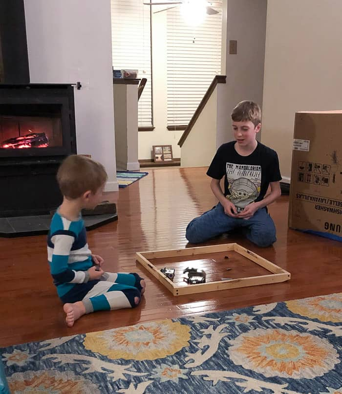 2 kids playing with cars in a living room