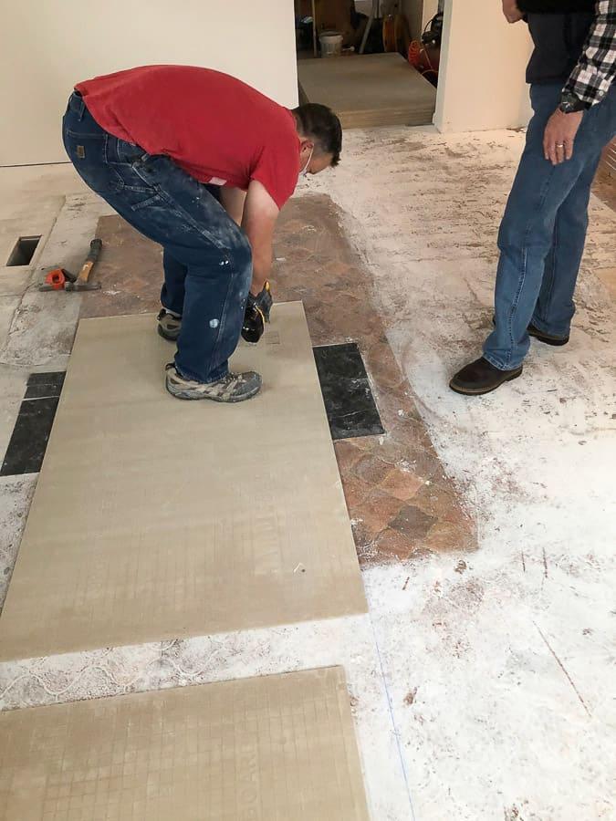 a man putting a piece of hardibacker on a floor