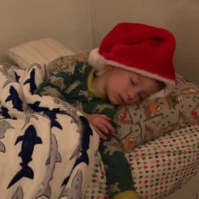 a little kid sleeping with a santa hat on