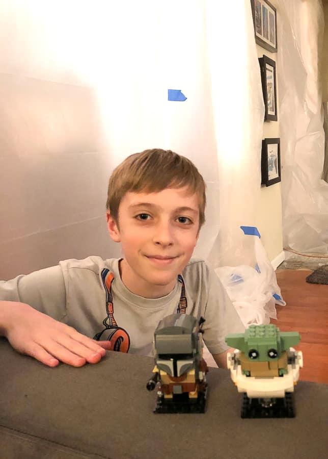 a boy with 2 star wars legos