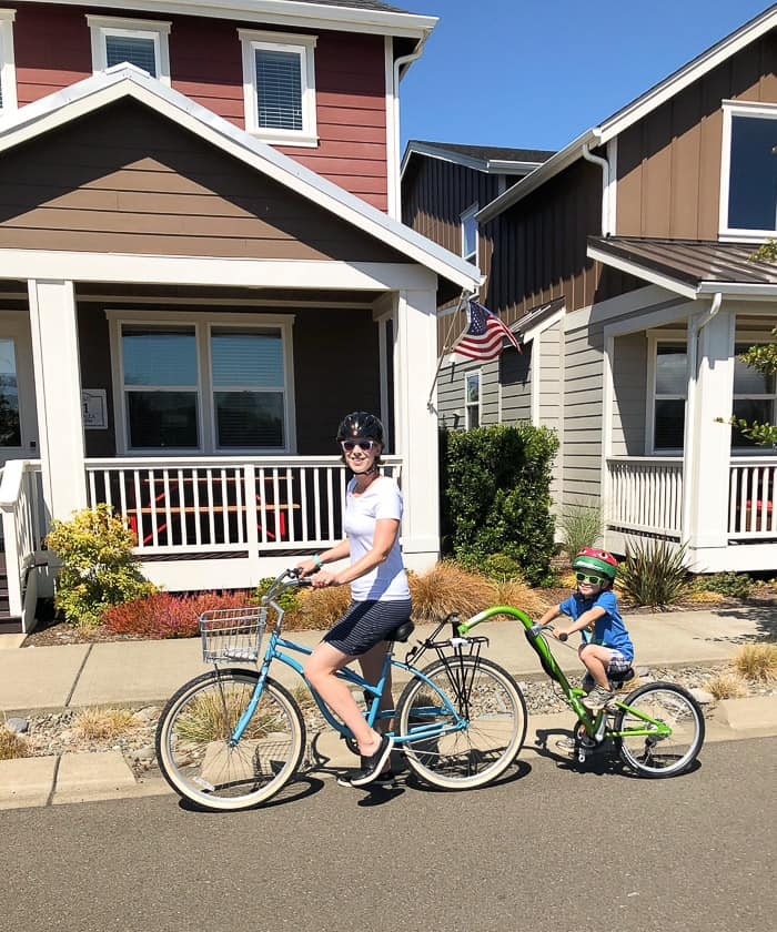 a mom and her son on a bike in front of a beach house