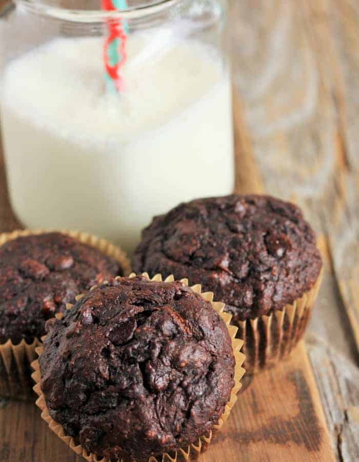 3 chocolate muffins on a board with a glass of milk