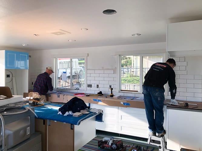 2 men tiling a kitchen wall