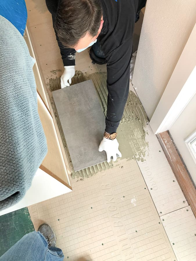 a man laying floor tiles