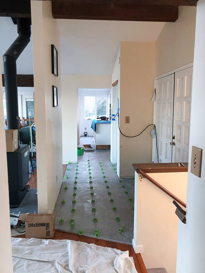 a kitchen under construction with floor tiles
