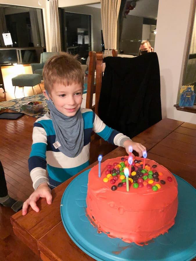 a boy with a red birthday cake topped with skittles