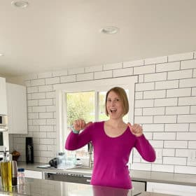 a woman in a purple top in a kitchen