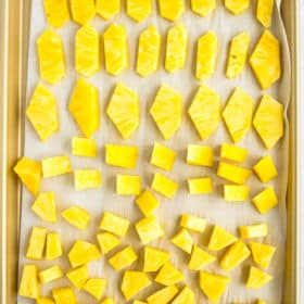 chunks of frozen pineapple on a baking sheet