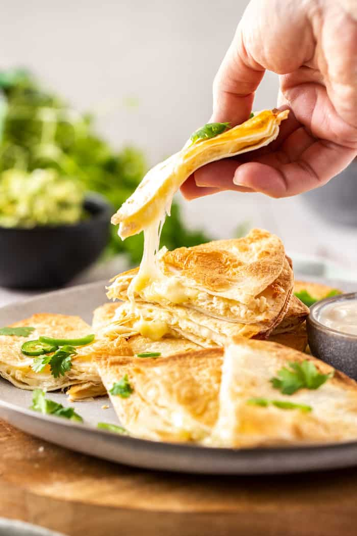 A hand holding a quesadilla with cheese being pulled