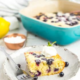 frozen berry cake on a plate with a fork topped with yogurt and a sprig of mint