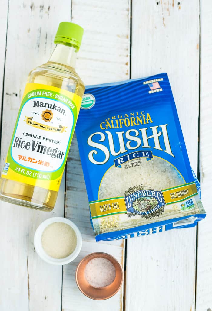 A bag of rice, a bottle of rice vinegar and 2 bowls on a white board