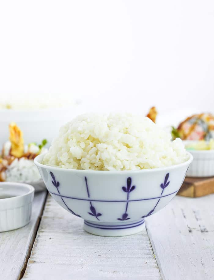 a white bowl with sushi rice on a white board