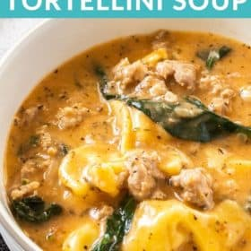 A white bowl with creamy tortellini soup