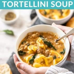 A hand holding a white bowl of Instant Pot Tortellini Soup