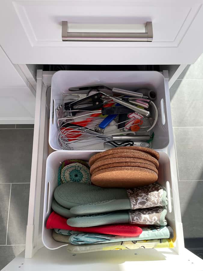 a kitchen drawer with pot holders