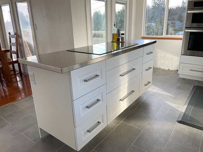 a white kitchen island with a stainless countertop