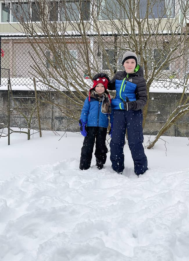 2 boys standing in the snow