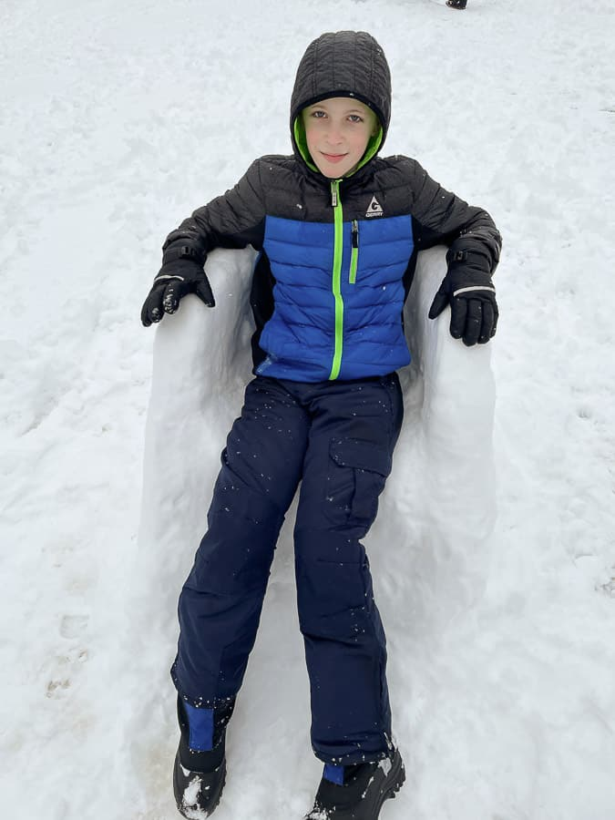 a kid sitting on a chair made out of snow
