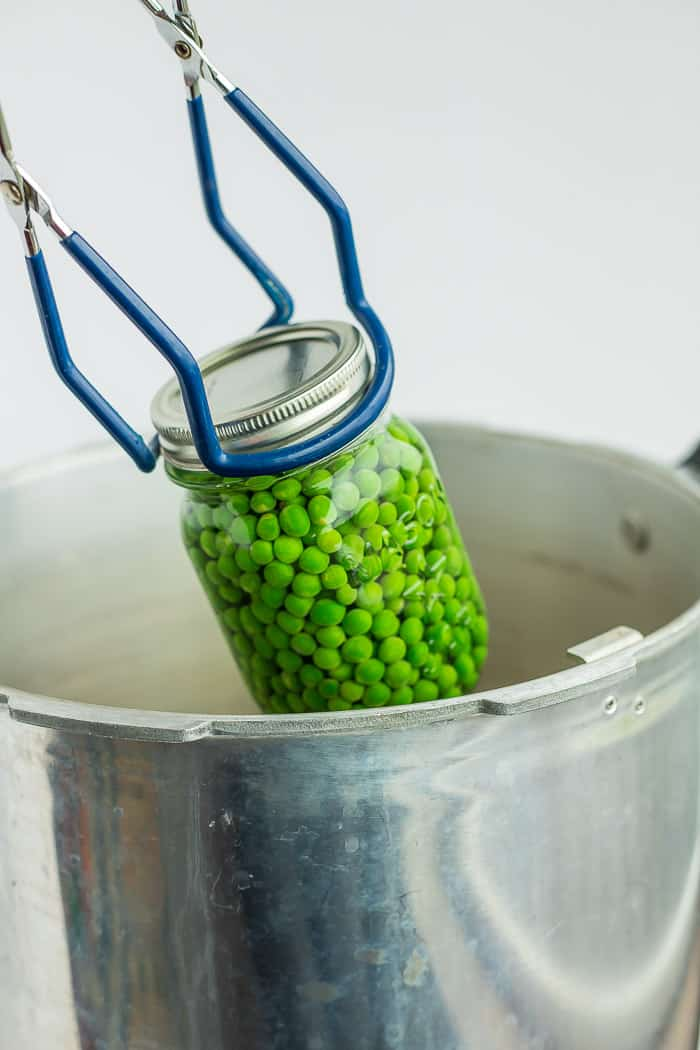 canning tongs holding a jar of peas