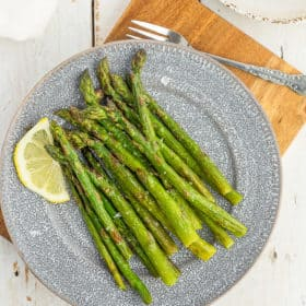 frozen asparagus on a grey plate with a lemon slice