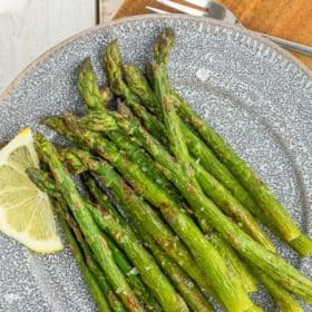 roasted frozen asparagus on a grey plate
