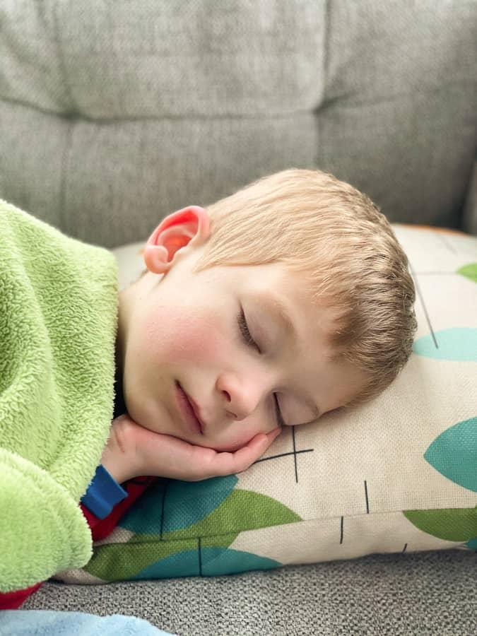a kid sleeping under a greentblankey