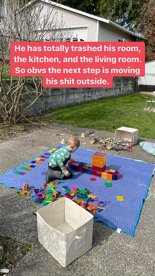 a kid playing outside with blocks on a blue blanket.
